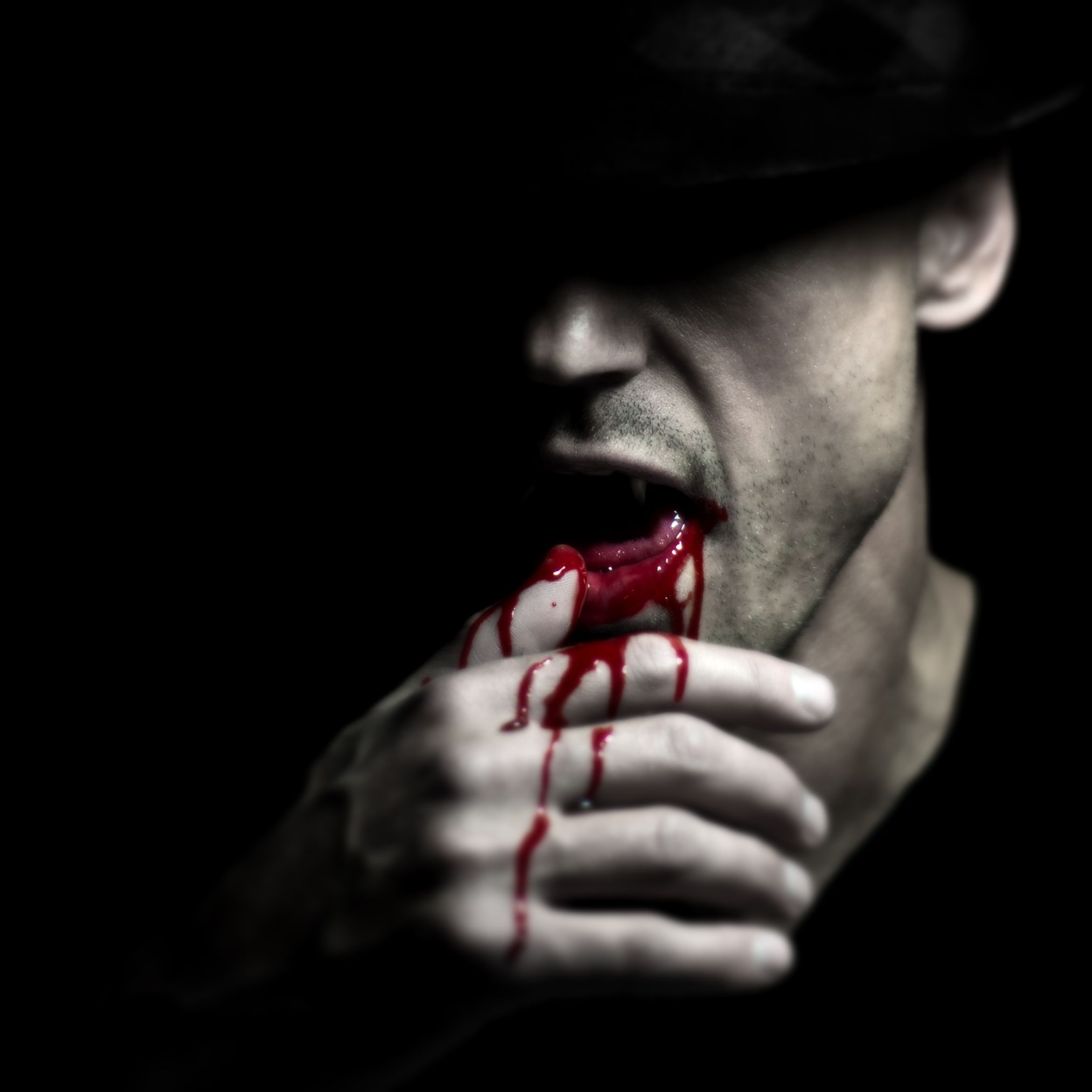 A vampire wiping the blood off of his mouth.