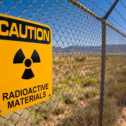 the fence of a nuclear facility with a radioactive sign