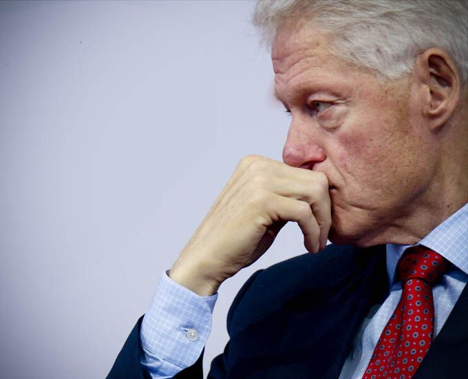 Color photo of Bill's left profile with chin in right hand as he listens