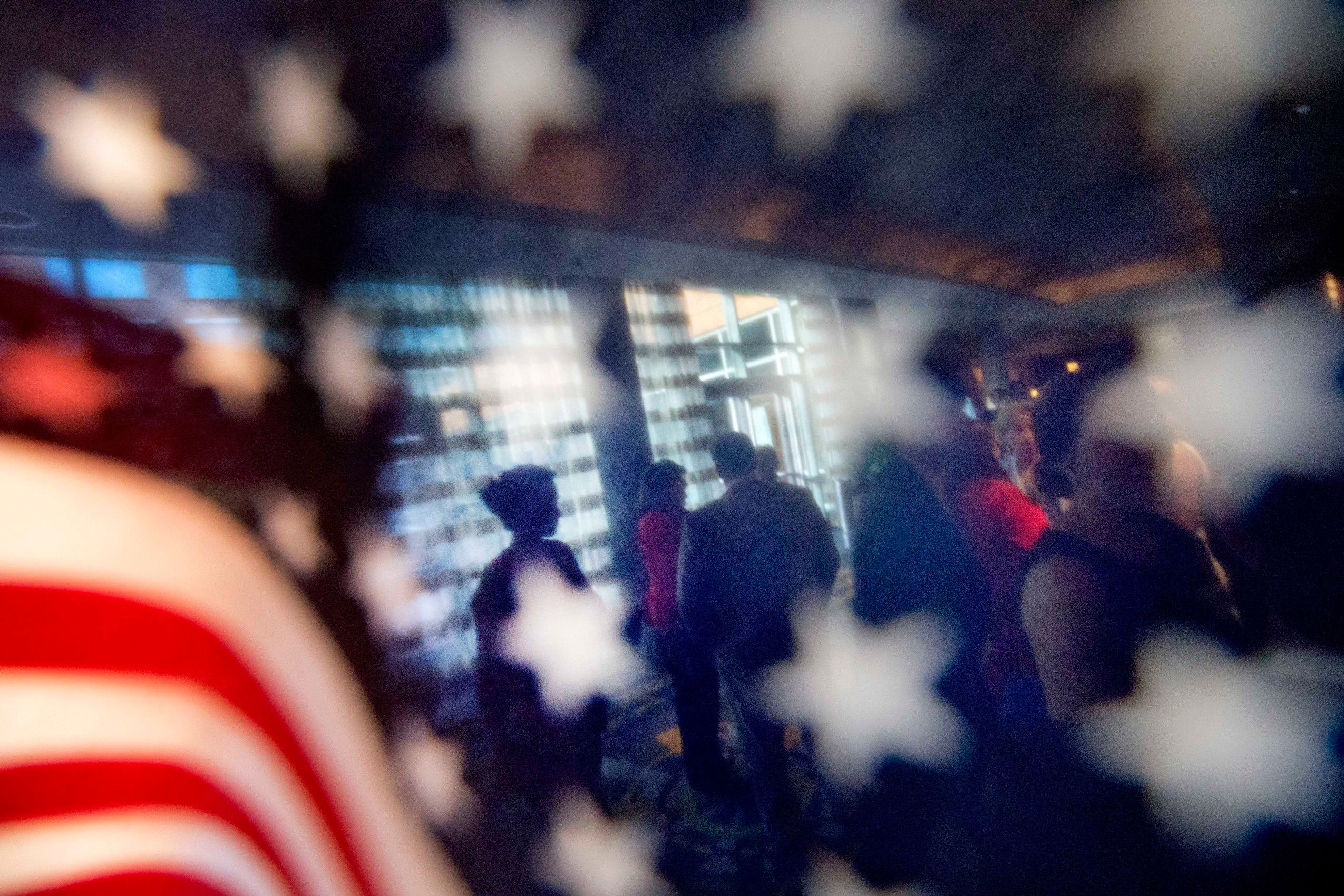 American flag in foreground with people being seen through it