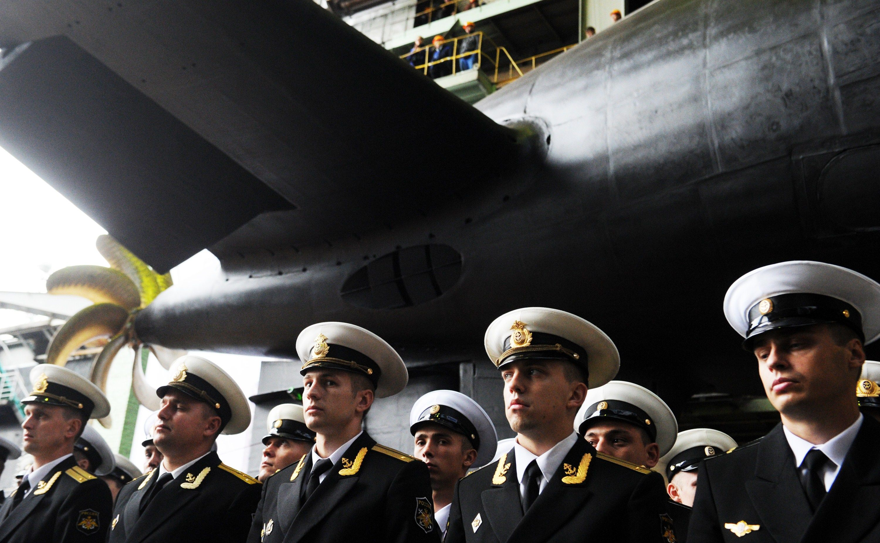 A row of Russian navy officers stand in formation in front of a submarine