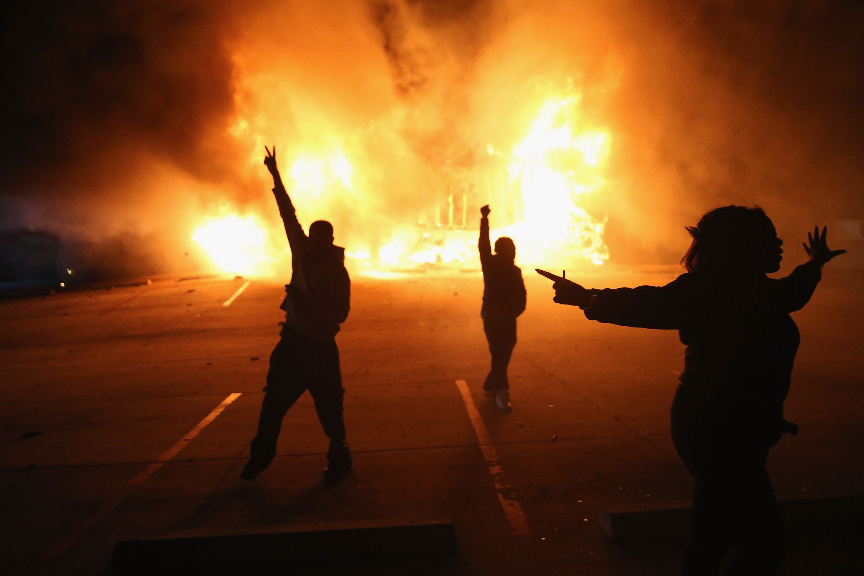 Protesters demonstrating in front of a burning business
