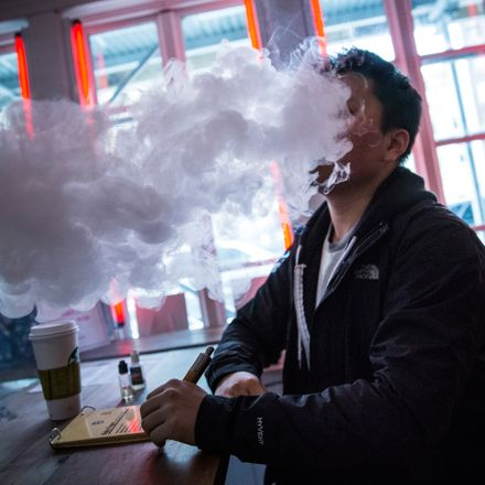A man sits in front of a bright window smoking an e-cigarette and releasing a huge cloud of vapor into the air.