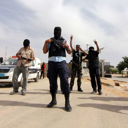 Men in masks holding weapons outside during the day posing for the camera