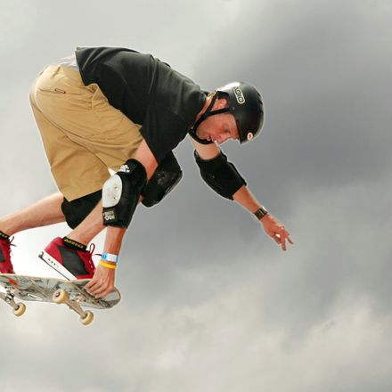 Tony flying in the air with his skateboard outdoors in color