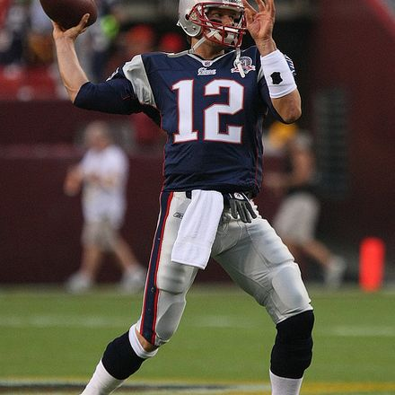 Tom Brady throwing a football in patriot uniform