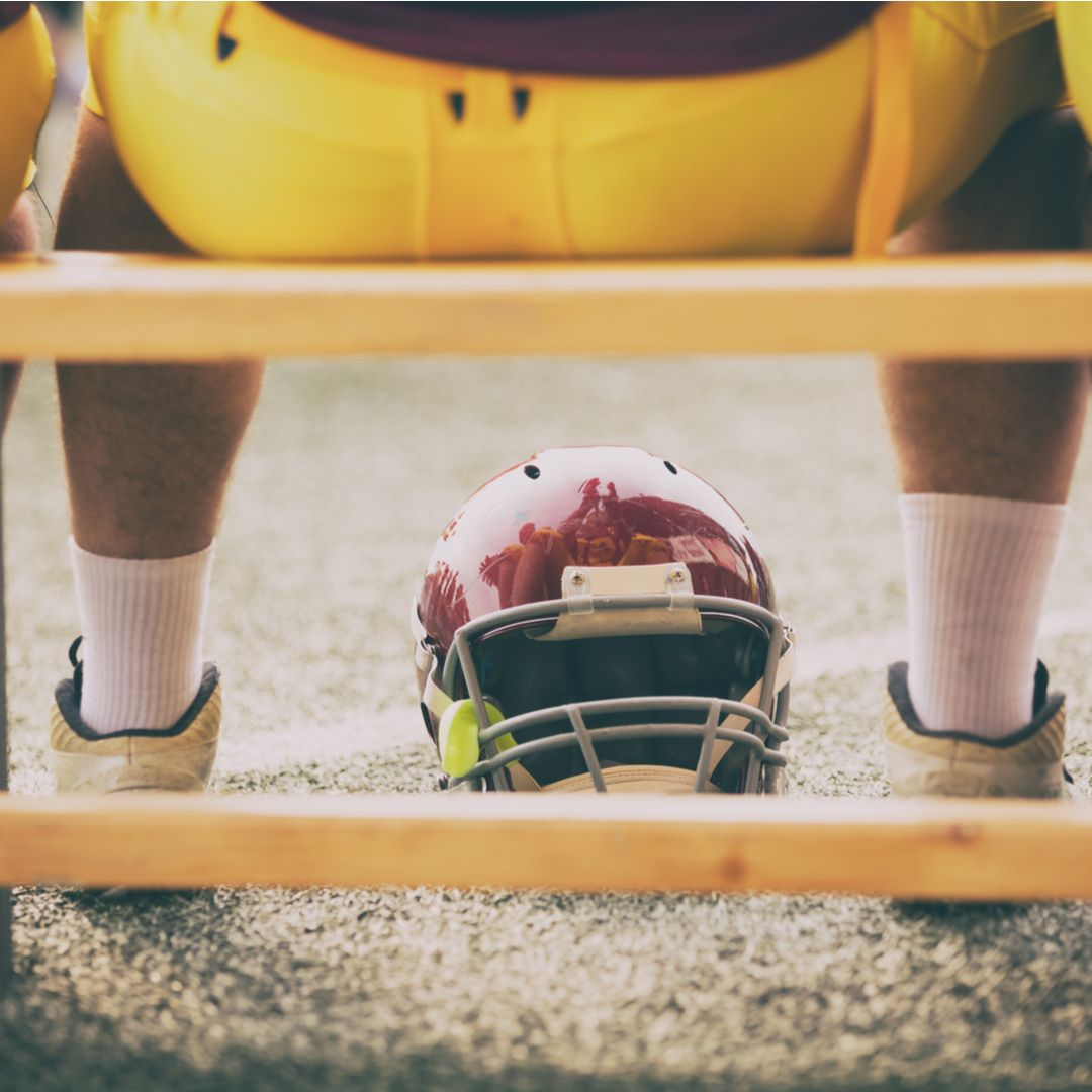 american football players on bench shutterstock 414227251