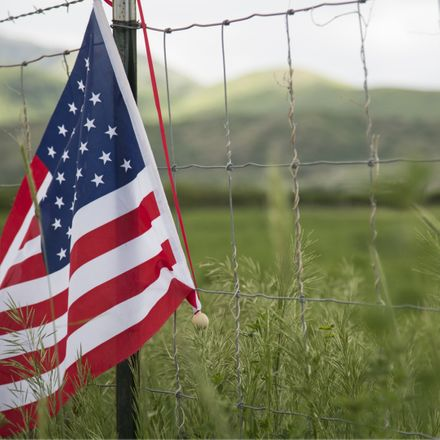 american heartland with flag and field shutterstock 145679114