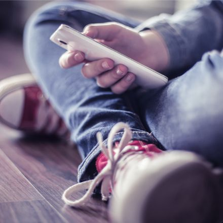 anonymous teenager looking at smartphone shutterstock 419832163
