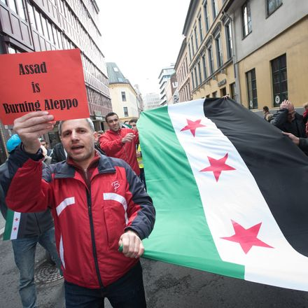 assad is burning aleppo placard at protest shutterstock 413837374