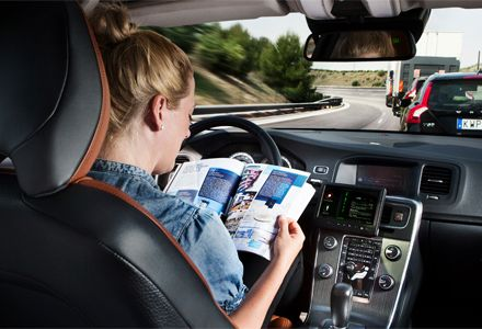 Woman reading while behind the wheel as the car is in DRIVE