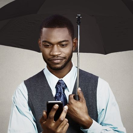 businessman with smartphone and umbrella 199985336