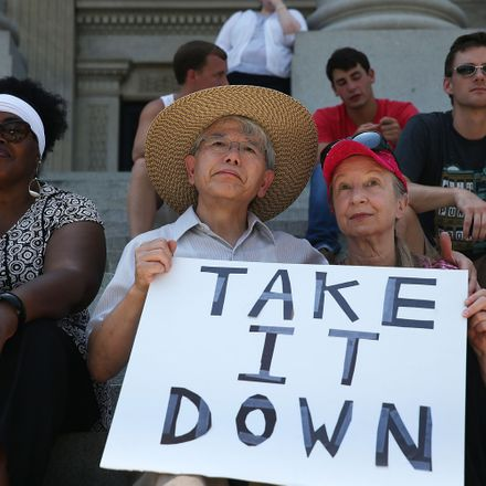 Anti-Confederate Flag protesters sit on the steps of South Carolina's statehouse as legislators vote to allow a debate on removing it from the Capitol grounds.