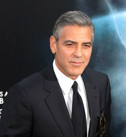 George Clooney in a suit outdoors at a red carpet event.