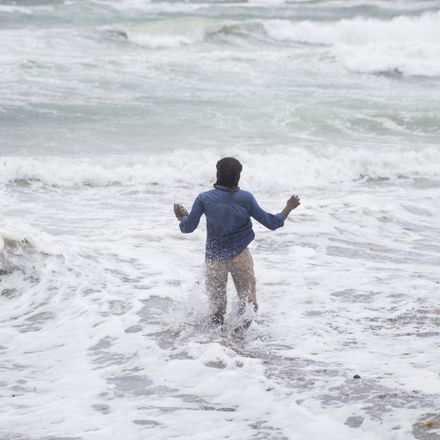 A person in Florida wades into the waves of West Palm Beach as Hurricane Matthew approaches. Source: Getty