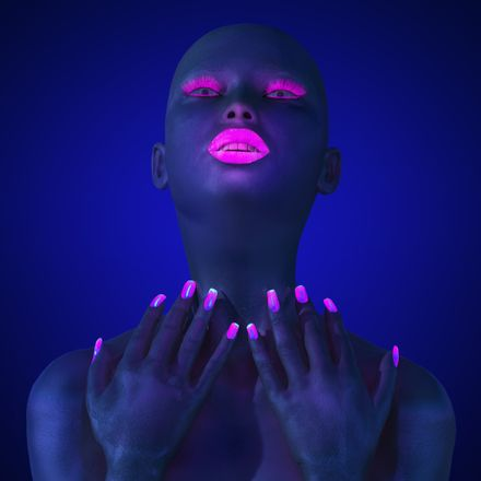 glowing woman with colorful nails and lips under blacklight shutterstock 244154485