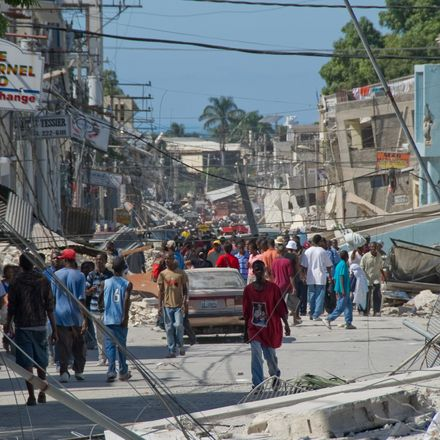 People wander the streets in front of the remains of a boarding school in the downtown area January 13, 2010 in Port-au-Prince, Haiti. Planeloads of rescuers and relief supplies headed to Haiti as governments and aid agencies launched a massive relief ope