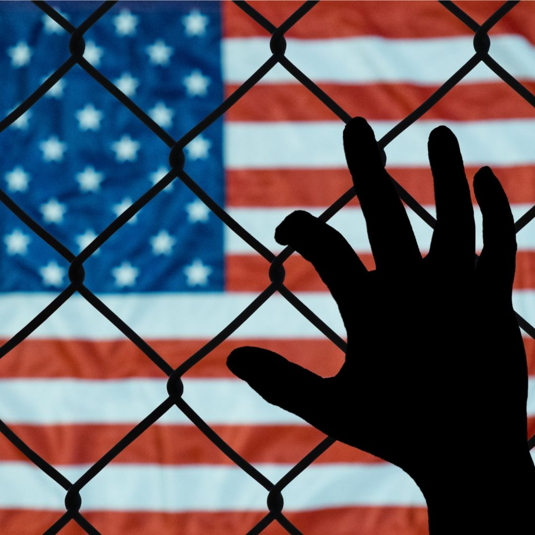 immigration us flag hand on fence shutterstock 719113522