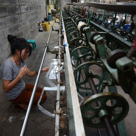 A worker prepares fibres to be used in the making of silk fabrics at a production unit on December 21, 2013 in Bogor, Indonesia