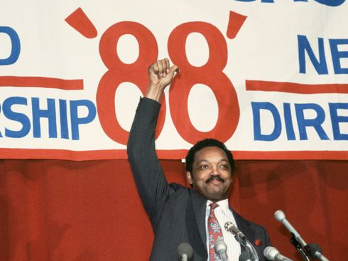 Color photo of Jesse Jackson at a podium with a campaign sign in the background. Jesse Jackson, Baptist minister and candidate for the Democratic presidential nomination in 1988, gives the thumbs up at the end of a campaign speech.
