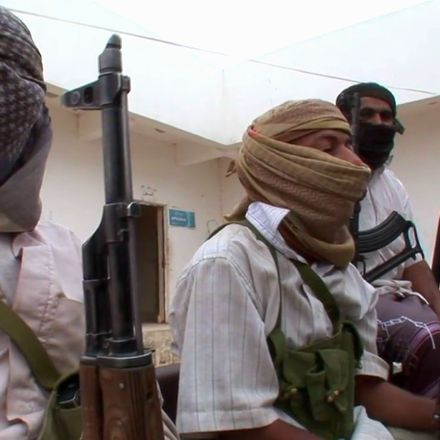 3 Al Qaeda members outdoors with their faces covered facing right of frame holding weapons.