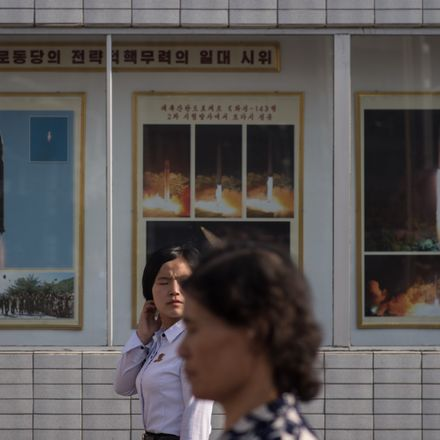 north koreans walk past missile launch posters getty images 851243604