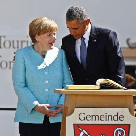 U.S. President Barack Obama (R) and German Chancellor Angela Merkel (L) speak to locals in front of the town hall in Kruen before the two leaders were scheduled to continue to the G7 summit at Schloss Elmau on June 7,