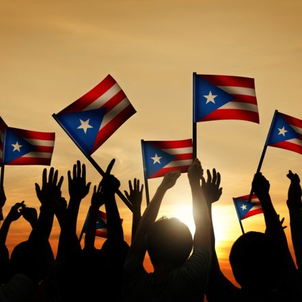 puerto ricans waving flags at dusk shutterstock 230260849