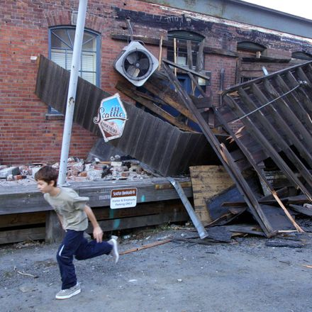 A boy runs past damage to the Chocolate Candy Manufacturing Company on the south side of downtown Seattle 28 February 2001, after an earthquake measuring 6.8 on the Richter scale hit the city and surrounding areas, causing widespread damage and dozens of