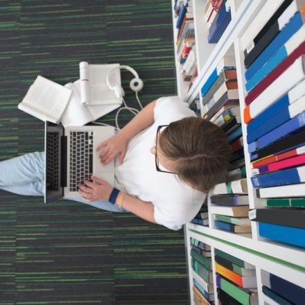 student on laptop in library shutterstock 420505687