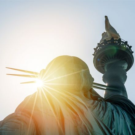 sun setting behind back of statue of liberty shutterstock 559730968
