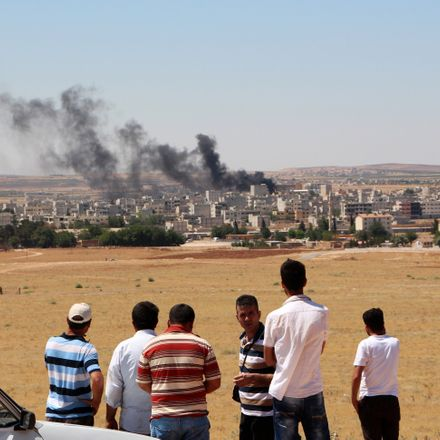 People look at smoke billowing in the Syrian town of Kobane from the Turkish side of the border in Suruc in Sanliurfa province on June 25, 2015