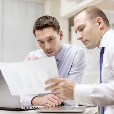 two white male office workers with computer looking at paper shutterstock 197885714