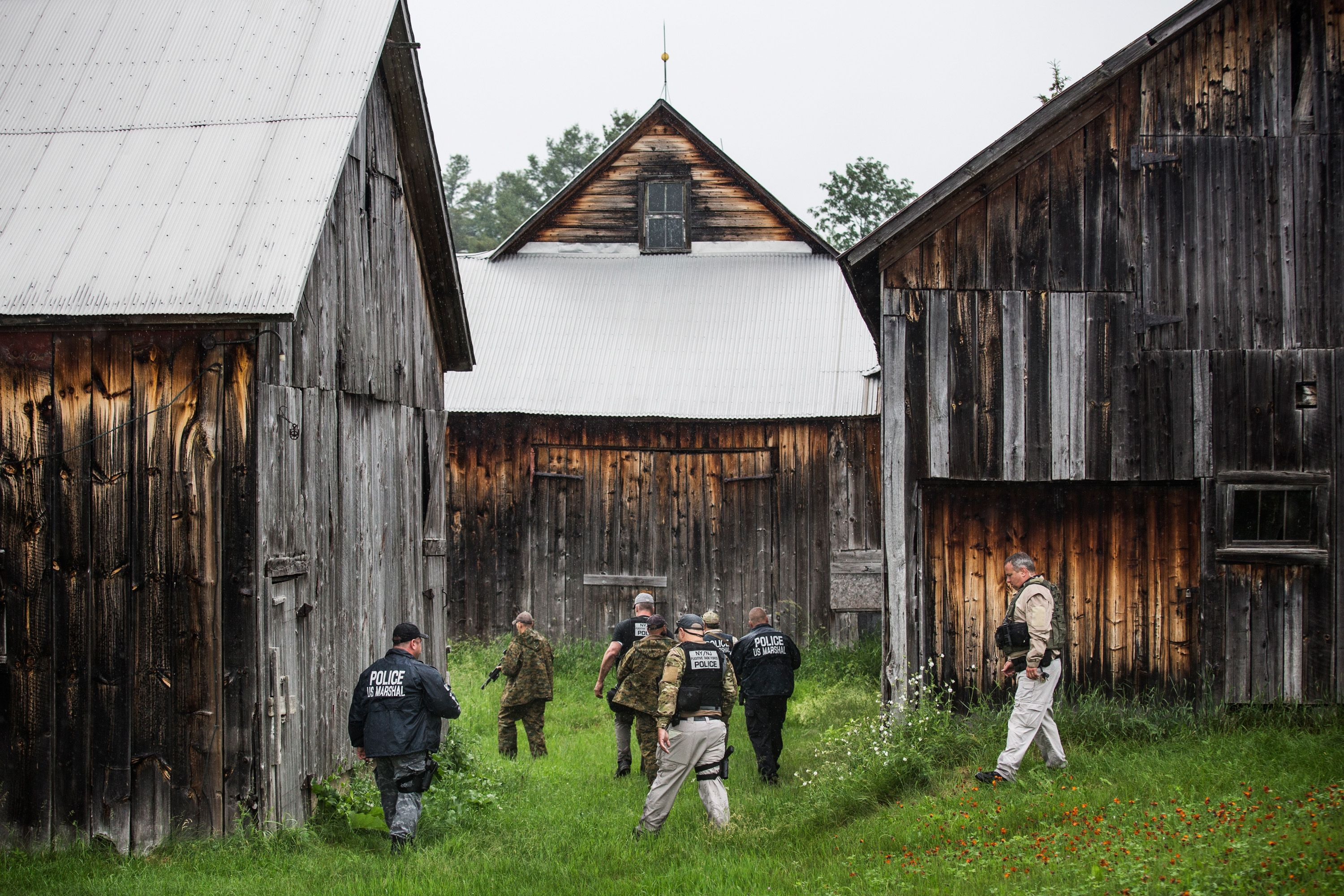 A task force of U.S. Marshalls and police officers go door to door searching for two escaped convicts on June 16, 2015 outside Dannemora, New York.
