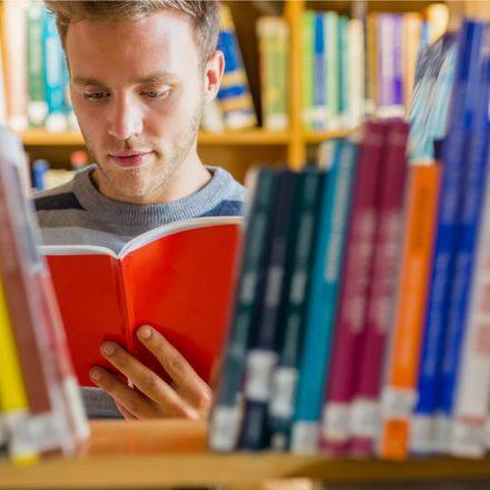 young man reading book in bookstore or library shutterstock 162685292