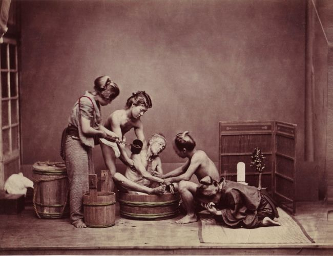 BW image of 3 people washing a body in a wooden bathtub