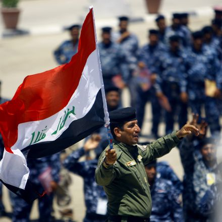 Soldier waves Iraqi flag.