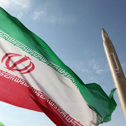 Iranian flag flutters next to a surface-to-surface missile