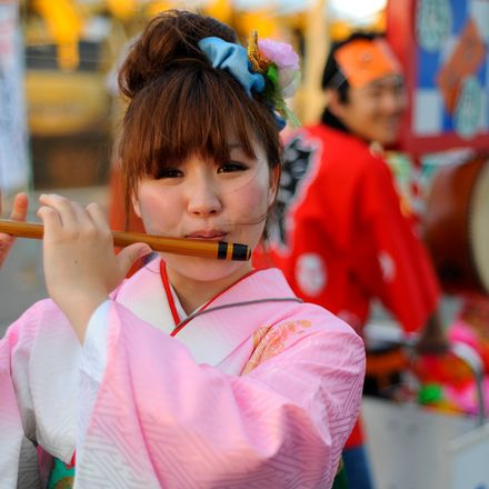 a young japanese girl in traditional outfit playingg flute during festival. fukuoka, japan, east asia