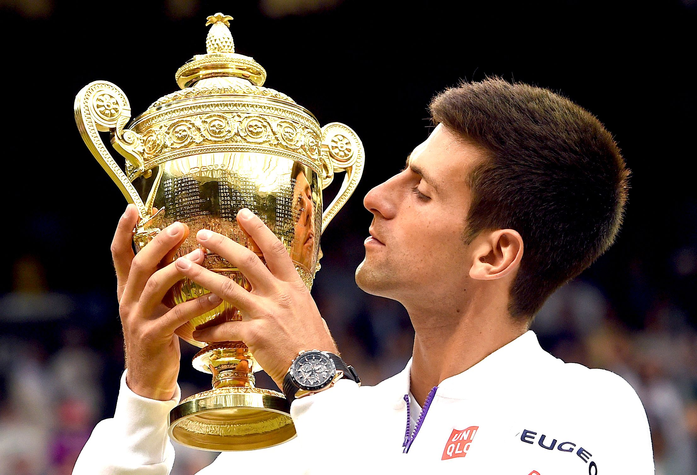 Novak Djokovic kisses his trophy.