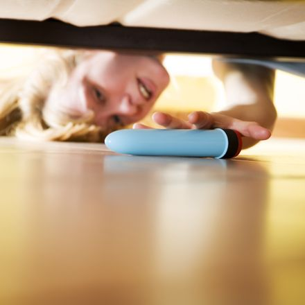 A girl looking under her bed to find a vibrator
