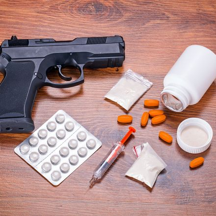 Drugs and gun on table shutterstock 158876066