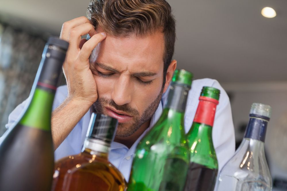 Drunk businessman alcohol bottles hangover shutterstock 178763324