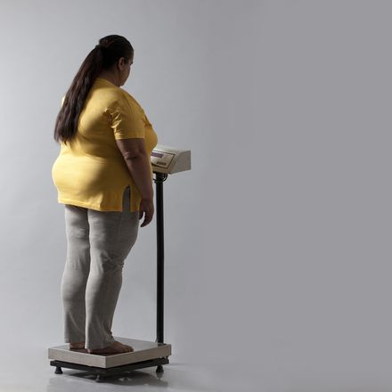 Obese woman on scale shutterstock 276168506