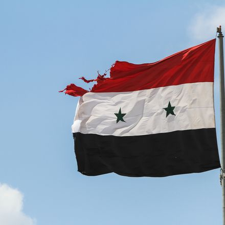 Syria flag damaged by gunfire shutterstock 327353651