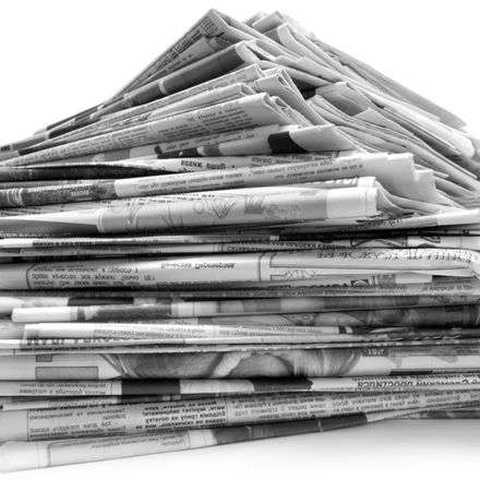 Pile of old newspapers isolated on a white background shutterstock 60998620