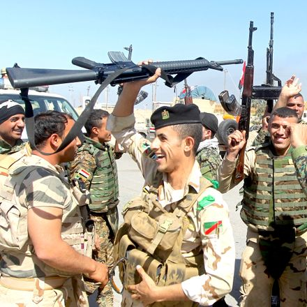 Iraqi soldiers raise their weapons, cheering progress made against ISIS on the outskirts of Tikrit.