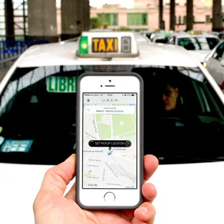 Uber appears on a smartphone with a taxi in the background.
