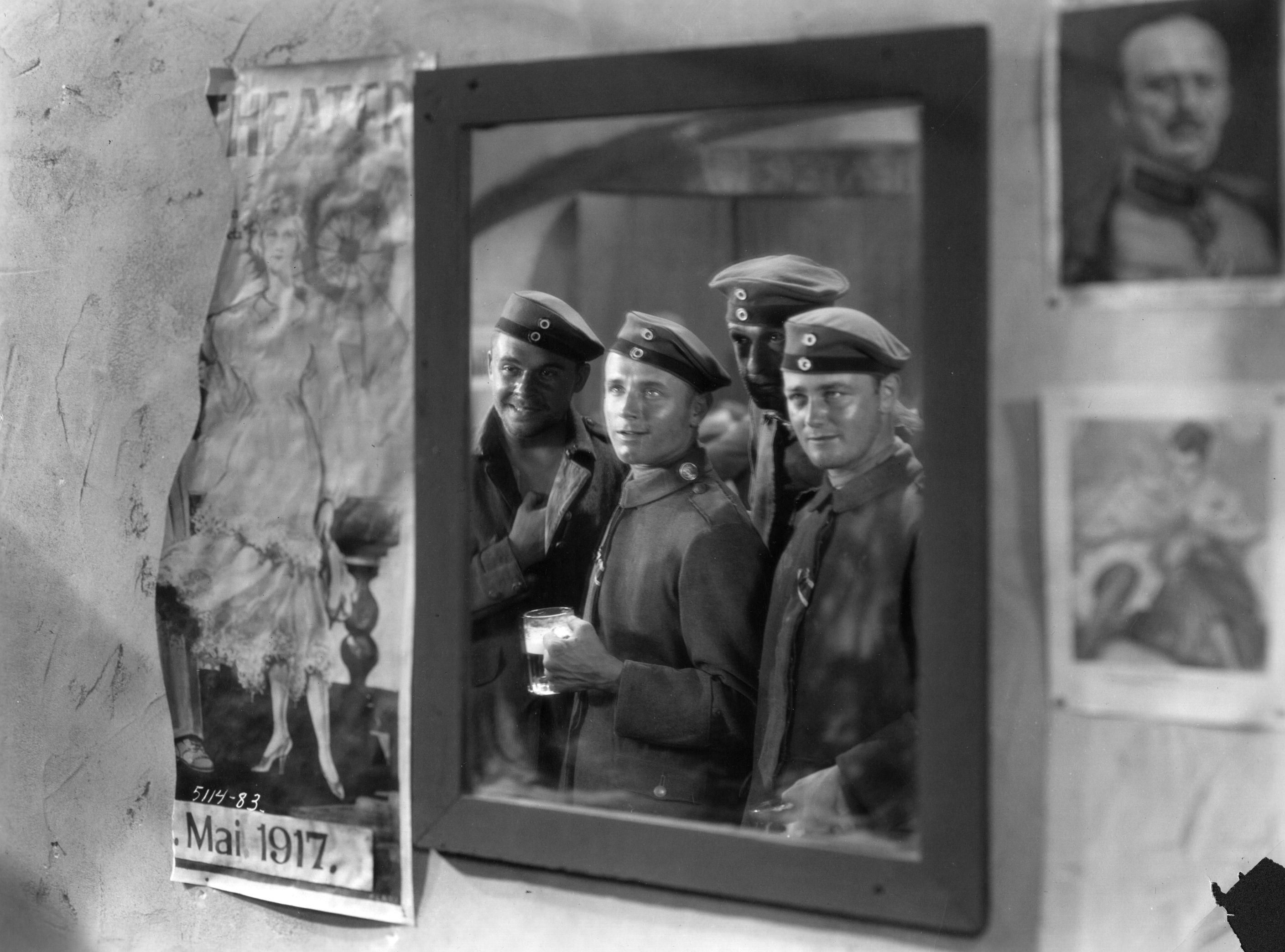 Scene from the movie All QUiet On The Western Front with 4 soldiers looking into a mirror