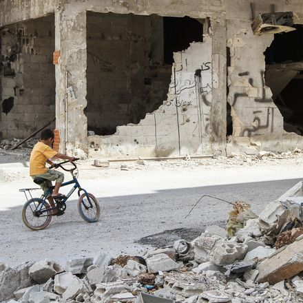 Homs, Syria, boy riding bicycle through rubble shutterstock 327353597